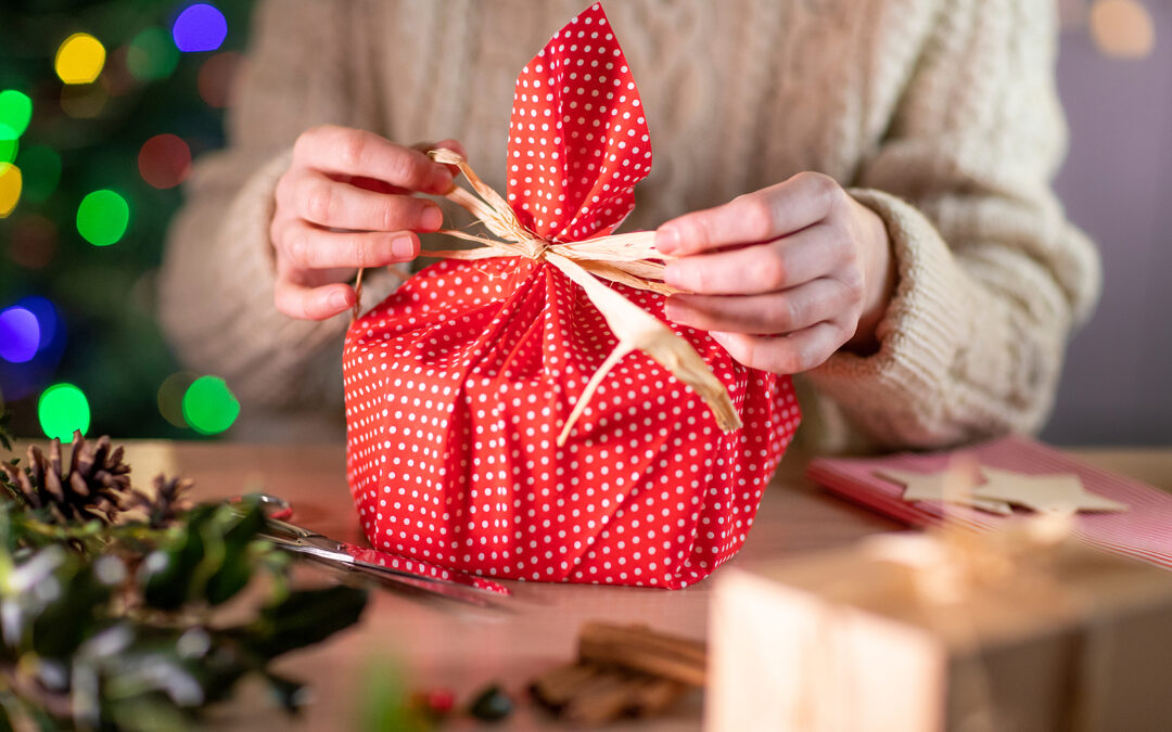 Someone wrapping a gift in reusable material teaching us how to shop sustainably this Christmas.