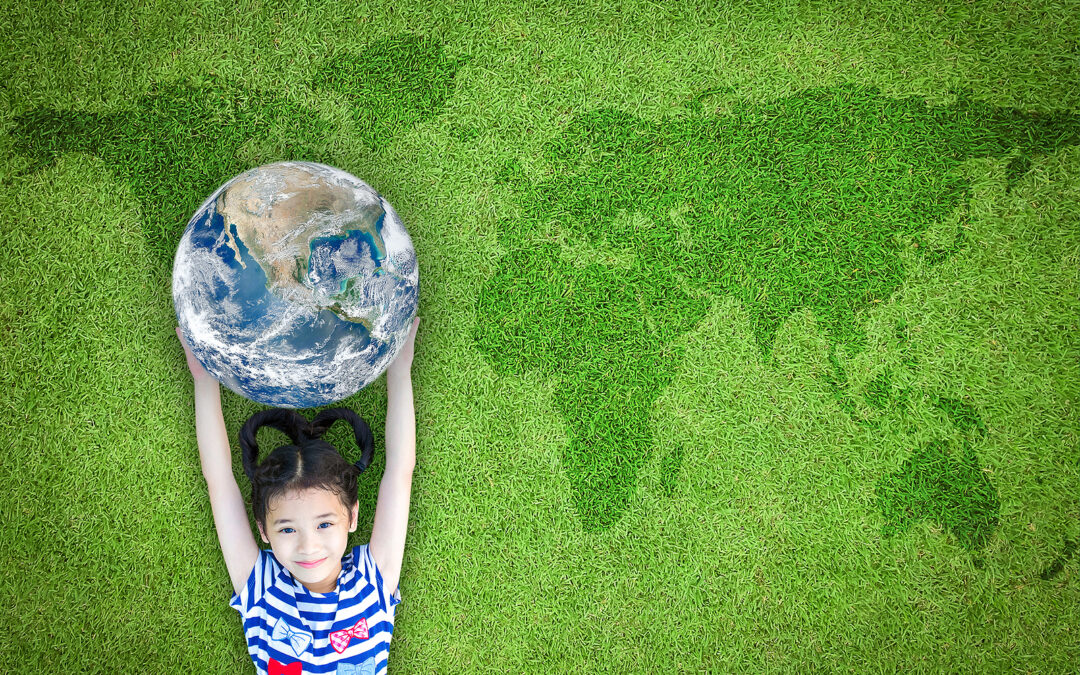 A third culture kid holding a globe on a world map made of grass.