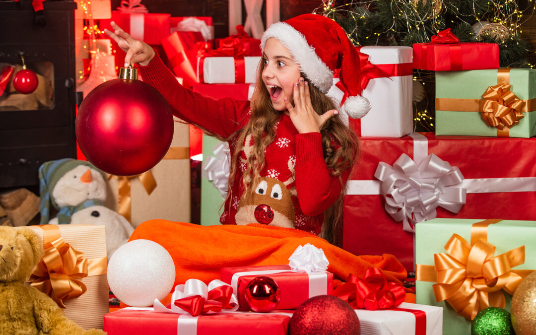 A young girl in a Reindeer jumper and santa hat surrounded by baubles and Christmas gifts for 8-10 year olds