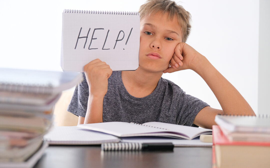 Pre-teen sitting at a desk taking a dyslexia test and holding up a written sign that says help.
