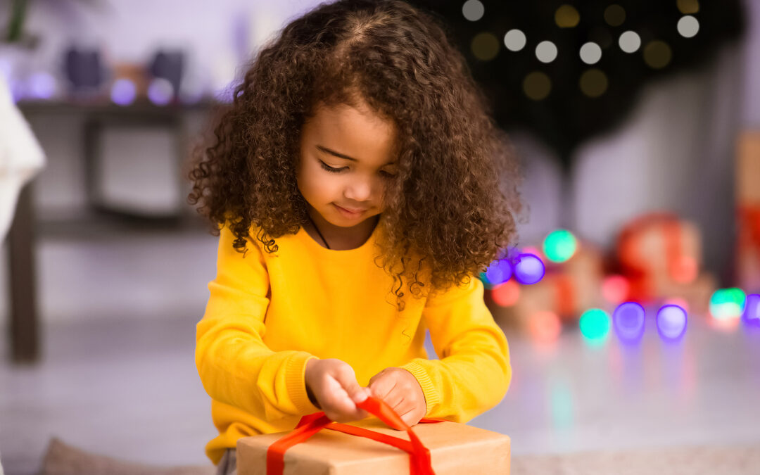 young girl opening one of the top Christmas gifts for 2-4 year olds
