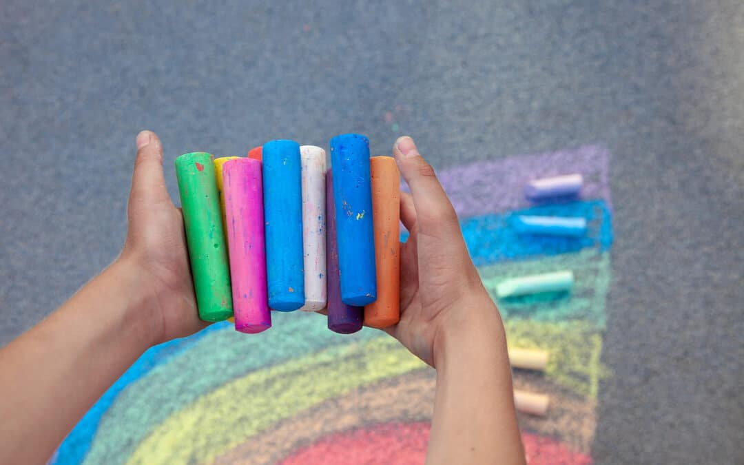 A child holding chalk. Symbolising a child showing symptoms of dysgraphia